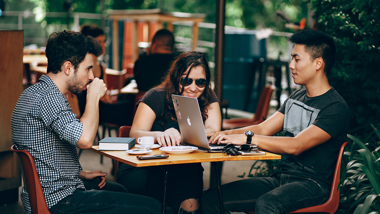 People sitting at a table working on a computer