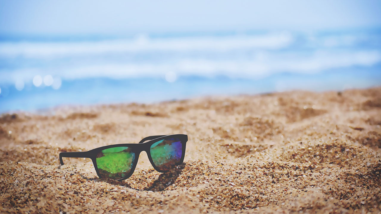 Sunglasses on a beach indicating a freelancers life