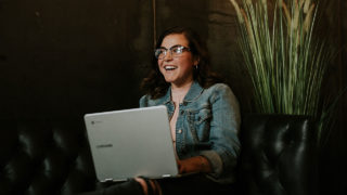 Person smiling in front of a laptop